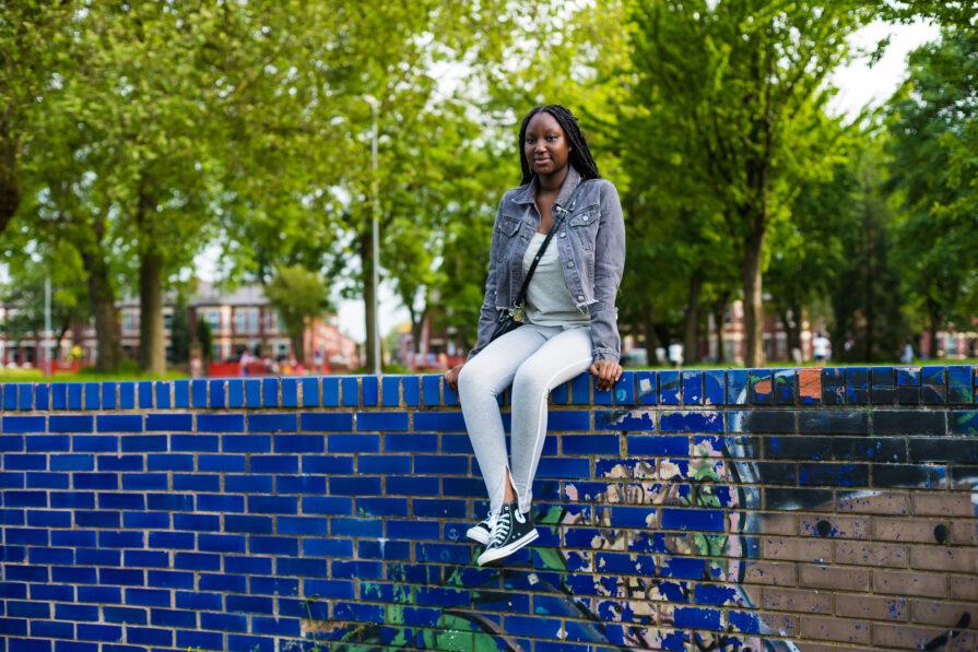 Kadija sitting on a wall